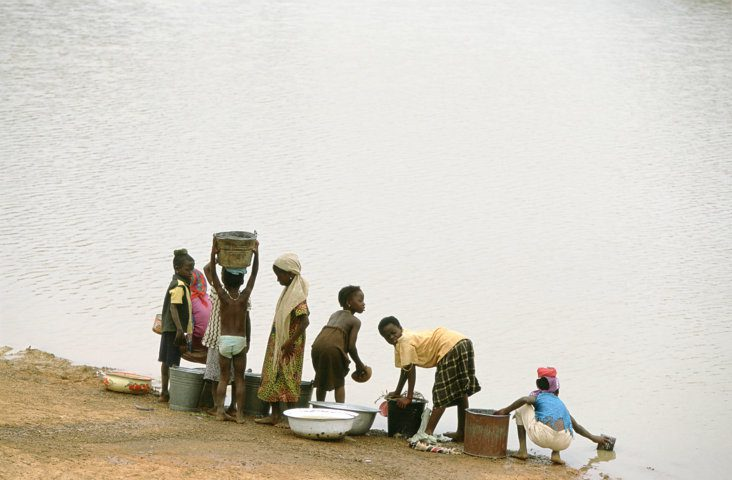 Children collect water from a lake. This lake in northern Ghana is also used by cattle, increasing the risk of contamination