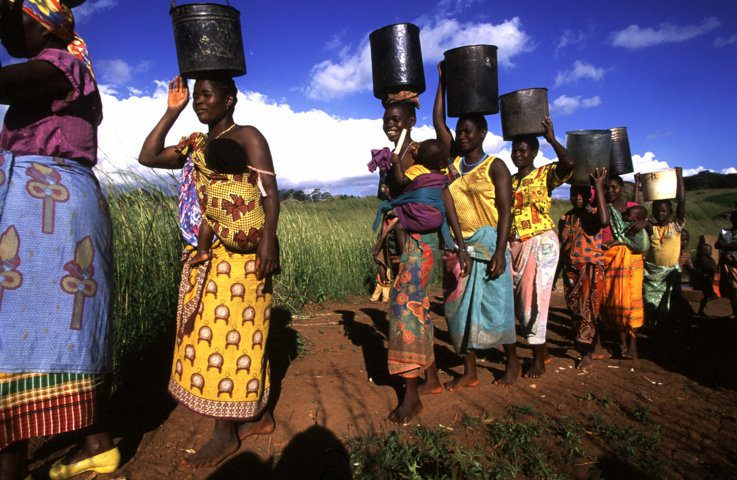 Women carry water from a well in Niassa province in north-west Mozambique. Over half the country's population lack access to a safe water source. On average, women in Africa and Asia must walk six kilometres to collect water. This significantly reduces how long they can dedicate to agriculture and other income generating activities