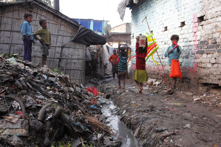 Kamla Nehru Nagar slum, Bihar. This state in north-east India is one of the least economically and socially developed in the country. Here, children carry water past an open sewer and a mound of rubbish. In India, 186,000 children die every year from diarrhoea largely caused by unsafe water and sanitation
