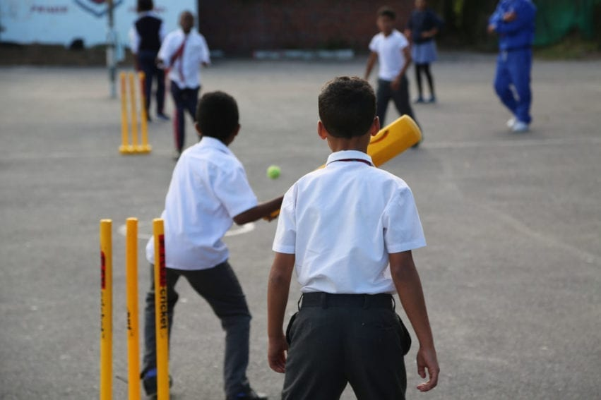 Children play cricket in the playground. Kids can attend after-school clubs and holiday programmes, which get them off the street and learning sport, the deputy principal tells me