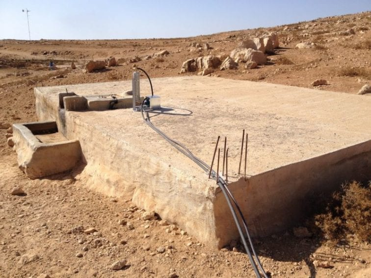 A pump and priming tank on top of a cistern in which rainwater is stored. Pipes carry water from the cistern to homes, where taps are installed. Before reaching the tanks, the water goes through particle filters to clean it. The new systems mean that children no longer have to carry heavy loads of water to their homes.
