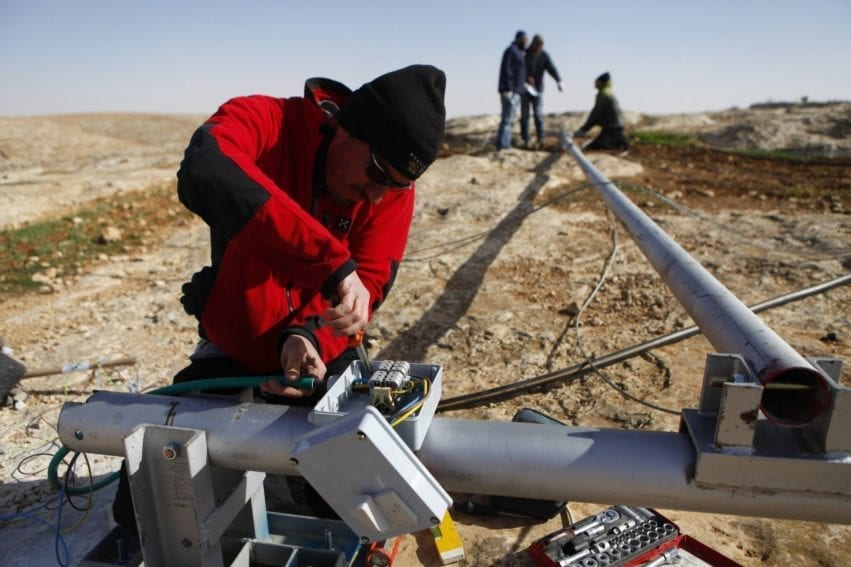 "A technician wires up a wind turbine before installation in the South Hebron hills. The villages here are in Area C of the West Bank, which is under Israeli control. Elad Orian, Comet-ME's cofounder, says Israel does not provide Palestinians with basic services ""as part of a political campaign to try and drive them off their land"""