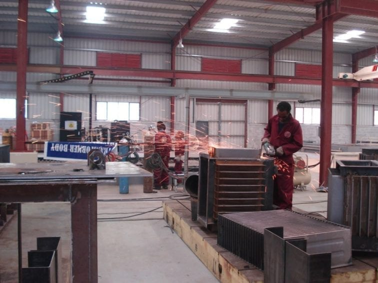 In the factory's main hall, workers assemble parts into the transformer casings. Transformers are used to change the voltage of an electricity supply