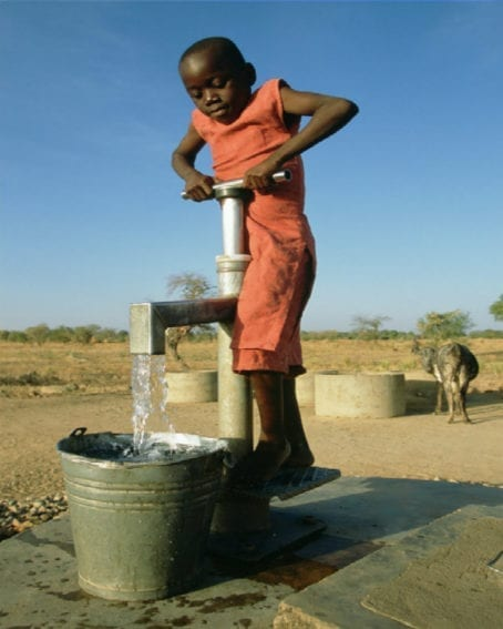 A girl pumps water at a well in northern Ghana. Many children in Africa miss school due to time spent collecting water. Girls are mainly responsible for collecting water for their families