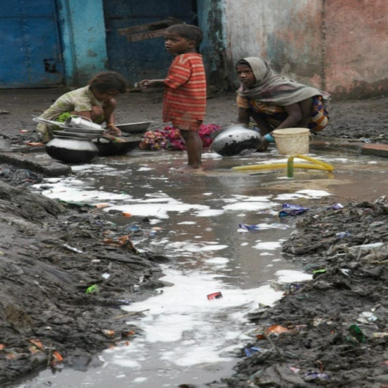 Children and women wash pots by a water pipe in Digha Maharajganj slum, India. The rubbish and waste water mix with the water from the pipe. These people belong to the Dalit 'rag picking caste'. In Bihar, the caste system is still in evidence today.