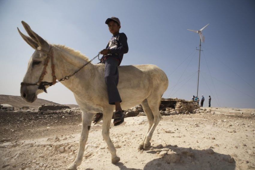 A young boy on a donkey near a wind turbine in Tuba village, Mount Hebron. The main livelihood in the region comes from animals such as goats and sheep