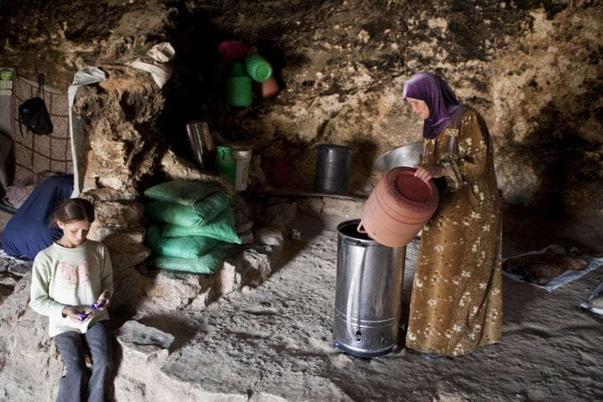A woman pours milk into a new butter churner, powered by renewable energy. Electric churners slash the time it takes women to make butter and cheese — one of the staple livelihoods here. Many of the villagers in the Mount Hebron hills live in caves such as this one in Tuba