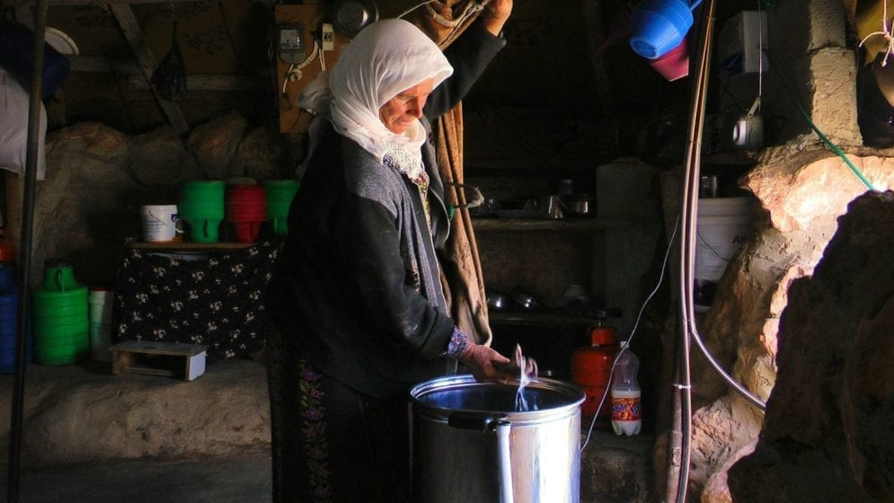 Hajeh Nuzha with a new butter churner in Sha'eb el Buttom village. The use of electric churners and refrigerators not only makes it easier to produce butter and cheese, but also leads to better products that sell for higher prices: family incomes have grown by as much as 70 per cent since the electric goods were introduced