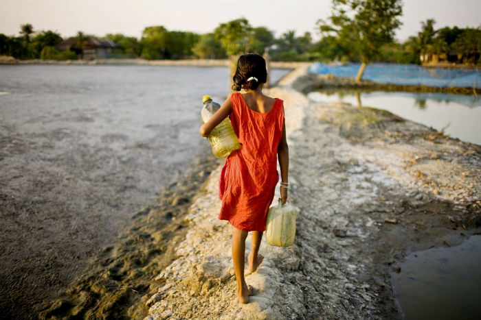 A girl carrying vessels home after collecting water from a pond