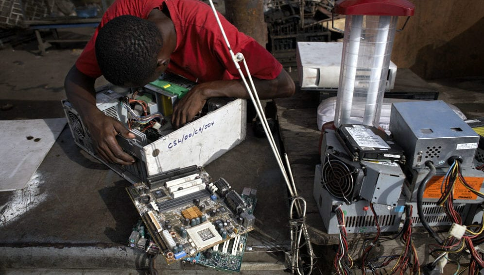 A man examines a hard drive at Agbogbloshie dump