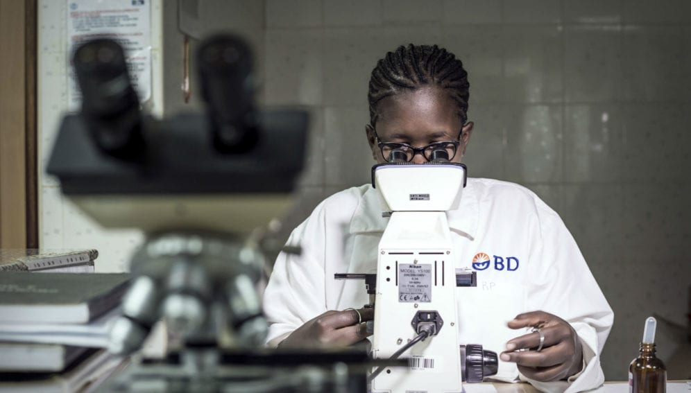 A woman examines a blood slide sample while testing for malaria