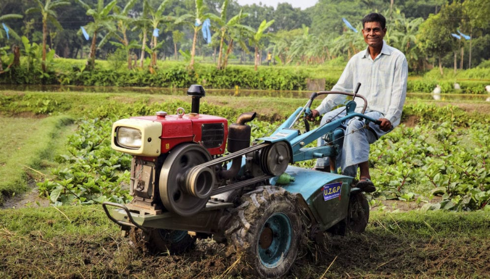 Abdul Khaleq with the agricultural machine he was given by a government NGO