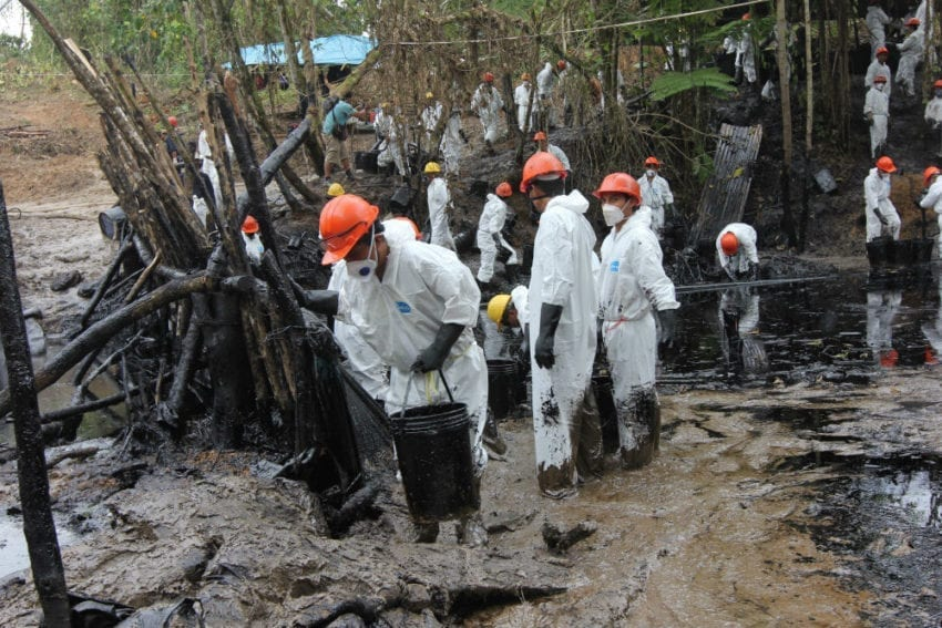 Workers hired from local communities collect some of the estimated 2,000 barrels of oil that spilled into a creek near the northern Peruvian town of Chiriaco in late January. Heavy rains washed some of the oil into the Chiriaco River, a tributary of the Marañón.
