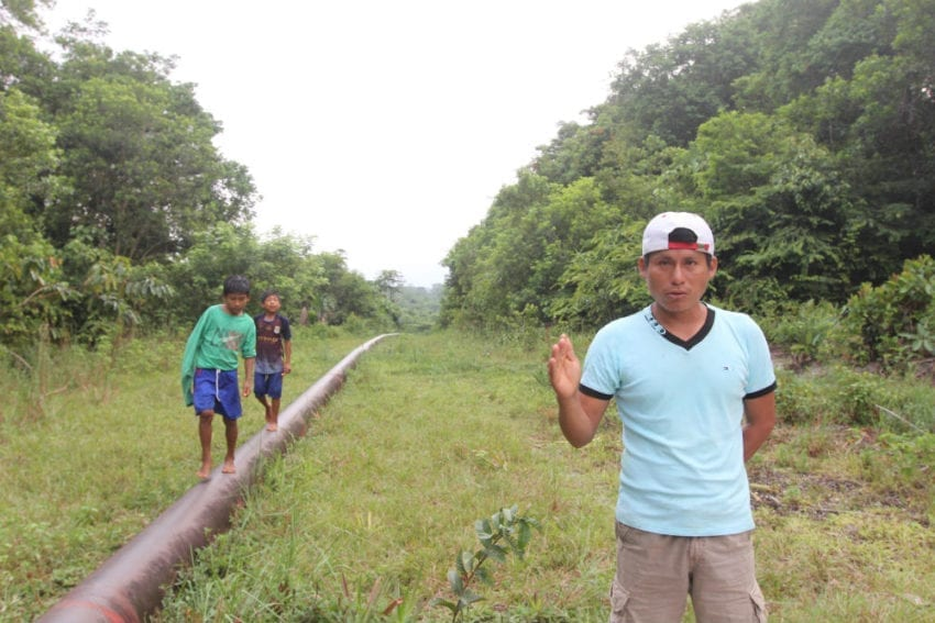 Elías Wasún, president of the Wampis indigenous community of Mayuriaga, stands on the pipeline that carries crude past his village from oil fields in Peru. A spill 13 km on the community's land, fouled a stream where residents and neighboring villages have traditionally fished and hunted.
