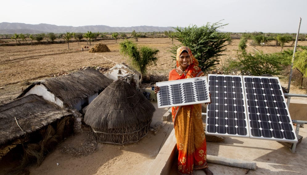 Indian woman holding solar panel