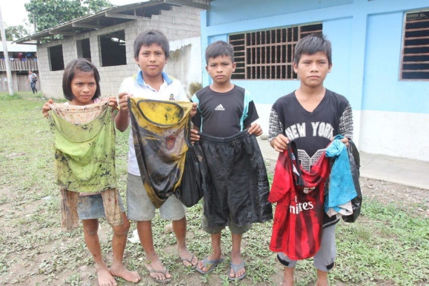 Children in the Awajún indigenous community of Nazareth display the clothes they were wearing when they scooped oil out of the river after a spill from a pipeline operated by Peru's state-run oil company, Petroperú.