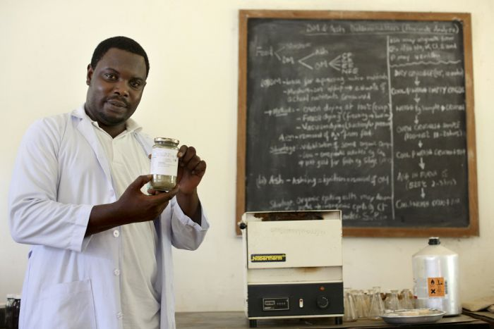 masters_student_holds_a_sample_of_dried_cassava_tops.jpg