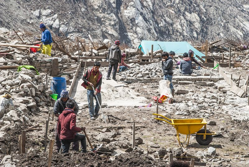 Langtang villagers rebuild homes beside landslide debris. Scientists fear more avalanches are in the making on the slopes high above the valley. But people have nowhere else to go because their only assets and land have been destroyed