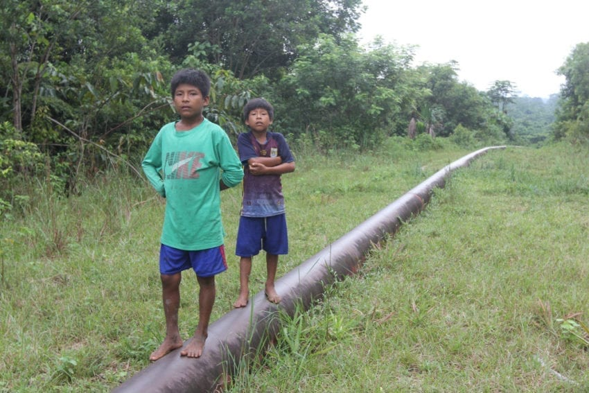 Children walk along a spur of the oil pipeline that carries crude across Peru.. The northern spur passes through the Wampis indigenous community of Mayuriaga, where about 1,000 barrels of oil spilled in early February, fouling land and streams.