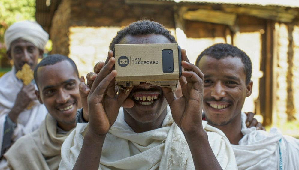 Priests take turns to view a phone within a virtual reality box