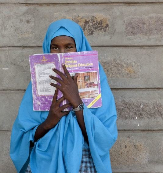 pupil holding a CRE book