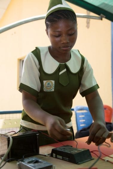 A pupil wires a solar cell, an important element within the science project her class is carrying out on domestic solar power