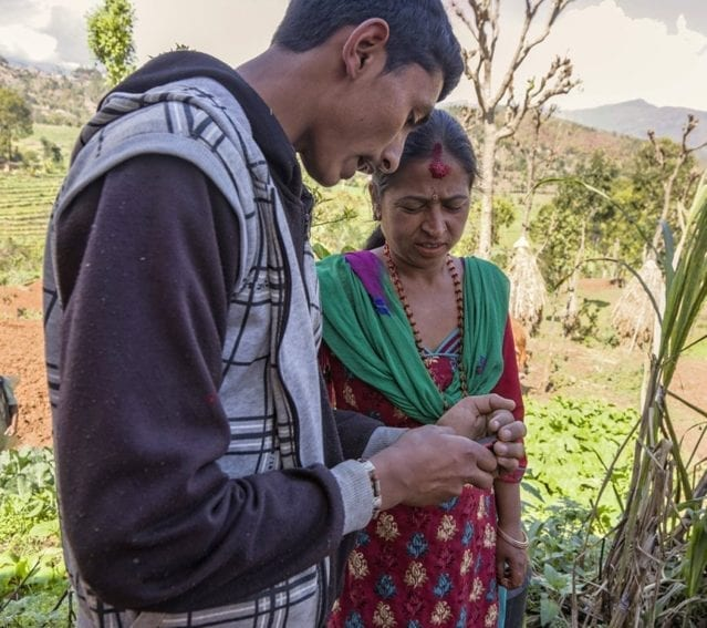 A woman and her son check crop prices on a mobile phone via text message. The message contains wholesale market prices from the Nepal Agricultural Research Council, helping farmers decide on the best day to sell their produce to maximise profit