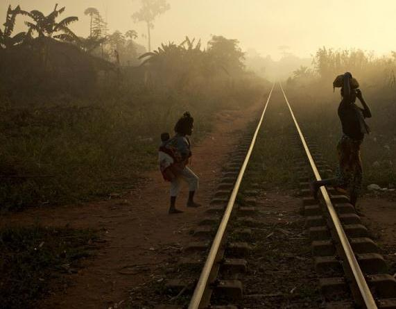 woman and a child carrying a baby cross the railway