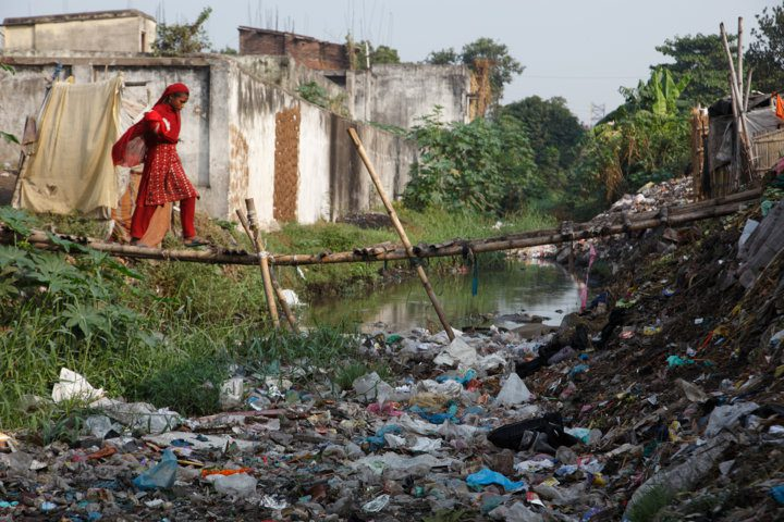 A girl crosses a makeshift bridge above an open sewer in the Kamla Nehru Nagar slum, India. The sewer is also used as a toilet and a rubbish dump. Young children have fallen off this bamboo bridge and drowned. Two-thirds of Indians, or 791 million people, lack access to adequate sanitation, according to WaterAid