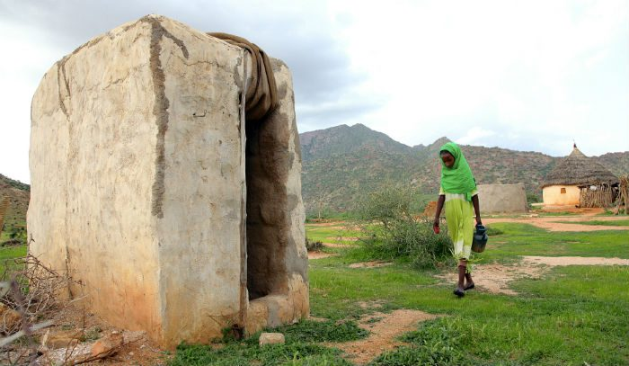 A girl walks towards the family toilet holding soap and water