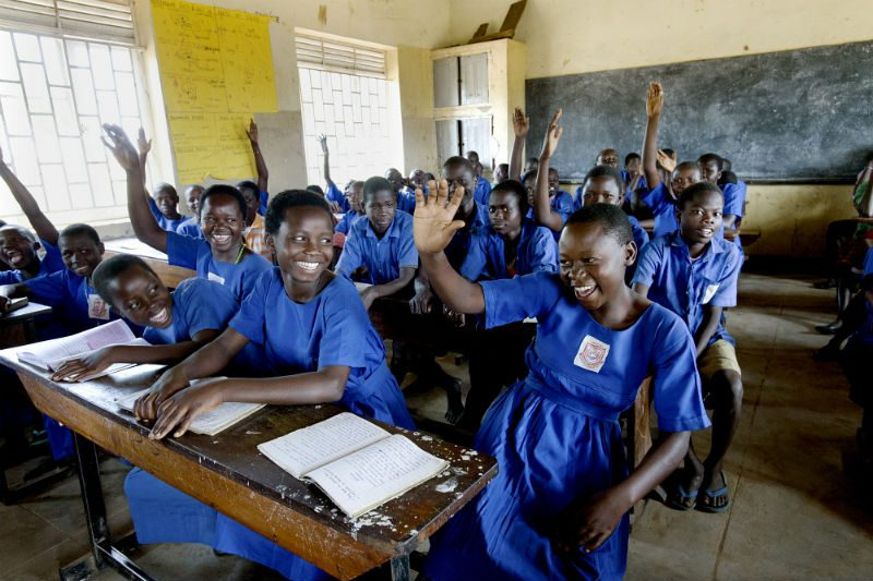 Girls raise their hands in response to the question