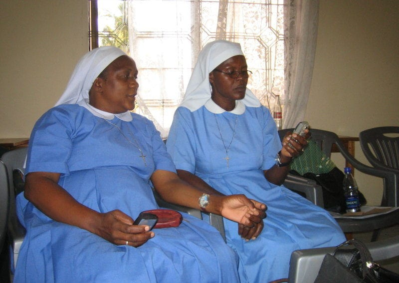 Medical sisters in Tanzania use a mobile phone while on a break of a Health Network meeting