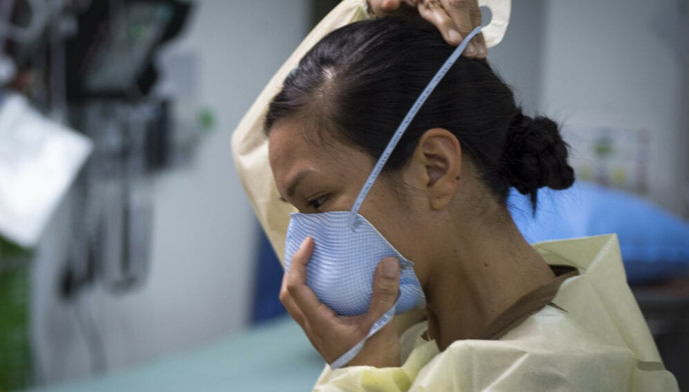 U.S. Navy Lt. Gail Evangelista, nurse, assigned to Naval Hospital Rota, Spain, dons a facemask prior to interacting with a patient at the Michaud Expeditionary Medical Facility (EMF) at Camp Lemonnier, Djibouti, April 16, 2020. Evangelista is part of a four-member team sent by Naval Forces Africa to augment critical positions within the EMF during the COVID-19 pandemic, enabling existing EMF staff to execute their primary mission of treating trauma patients. (U.S. Air Force photo by Senior Airman Dylan Murakami)