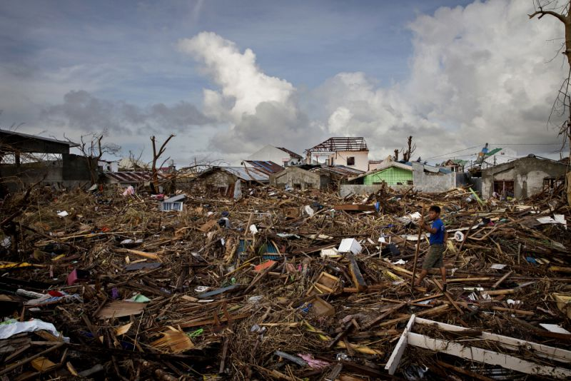 A man sifts through the debris of homes destroyed Typhoon Haiyan