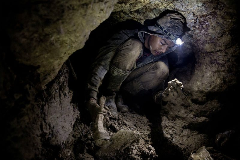 A young miner working in a narrow shaft