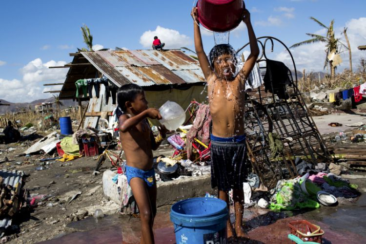 Children wash with water collected from a nearby well