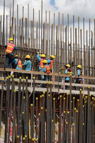 Thai and Lao workers insert reinforcing bars before concrete is poured to form the dam walls