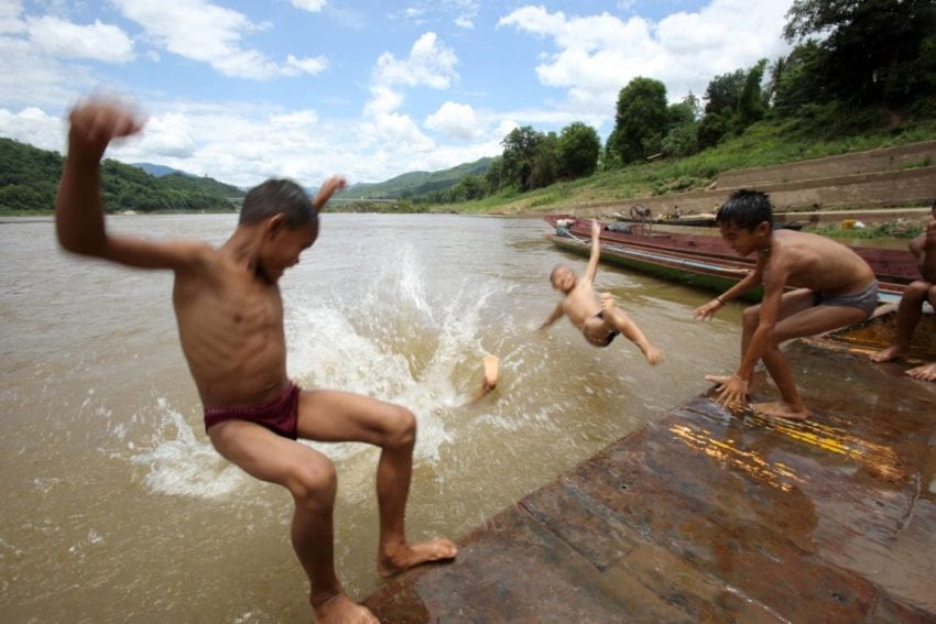 Children play in the Mekong near the dam
