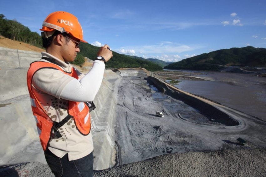 A worker photographing the 'fish ladder'. This is being built to help migratory species swim around the dam. One fear is that the dam will block the paths of many migrating fish such as the Mekong giant catfish. Some experts predict that this will wipe out many species as the 32 metre dam walls are too high for the fish ladder to work