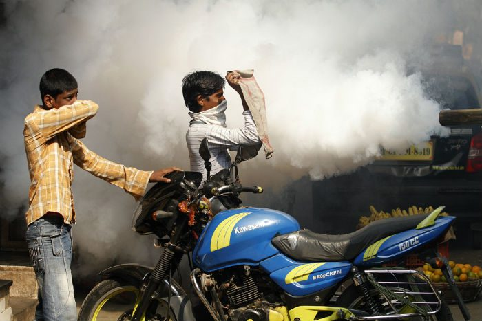 People try to protect themselves from the smoke as a truck fumigates