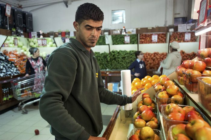Rafat arranges a display of fruit at a branch