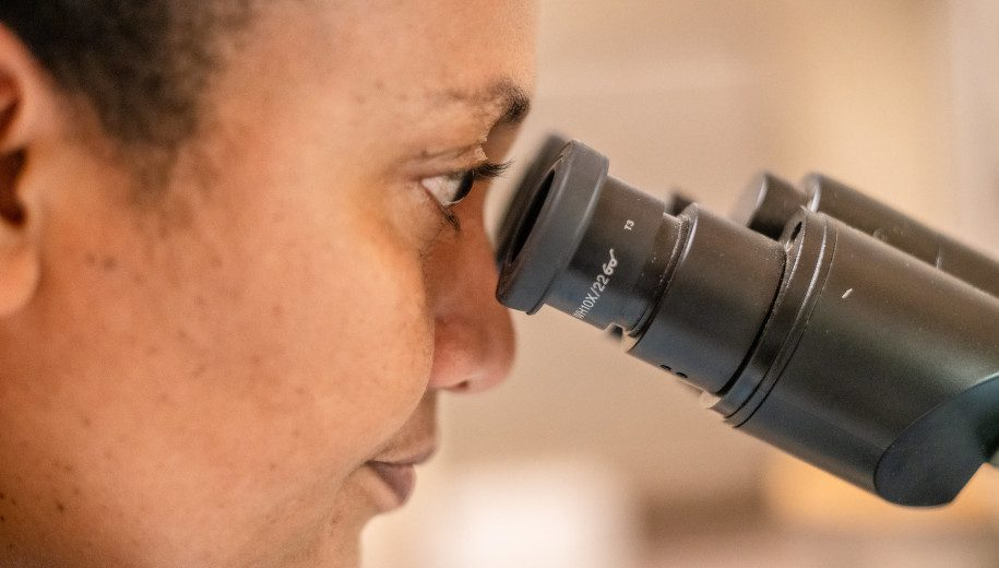 medical technician looking into a microscope