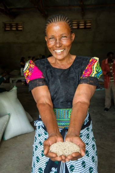 Broad smile: a female farmer smiling while holding the fruits of her labour that offer earnings and livelihoods for many smallholder families