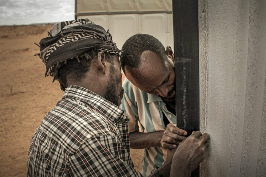 Two men at the camp assembling one of the flatpack shelters made by Swedish social enterprise Better Shelter. The shelters take four to eight hours to erect. Unlike tents, they are lockable