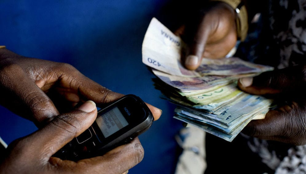 A customer uses his mobile phone to get cash from a Tigo Cash outlet