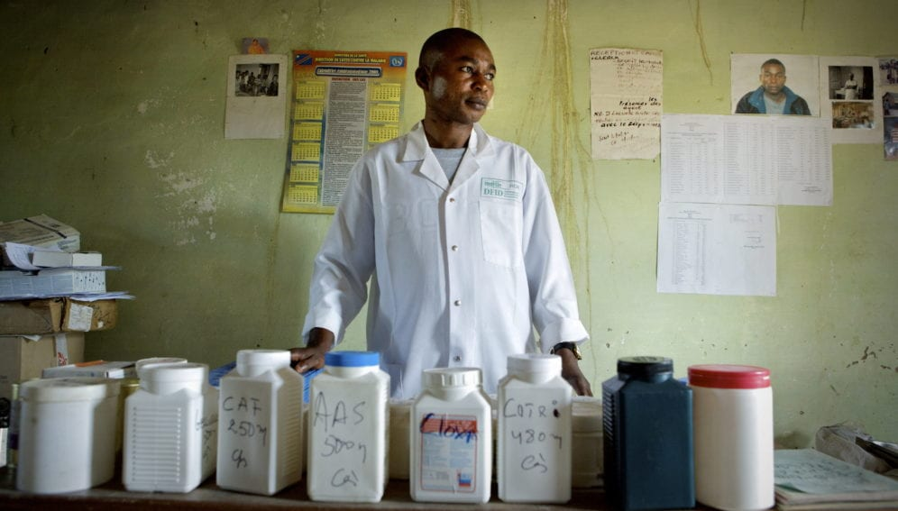 A nurse stands in front of medicines