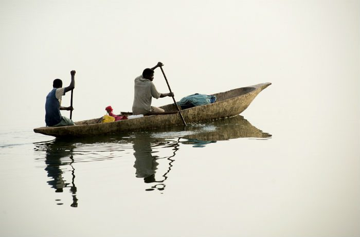 Men depart at dawn in a pirogue to go fishing among the mangrove