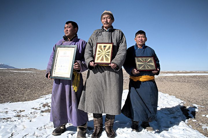 Batkhuyag Tseveravajaa, head of the Uvurkhangai community in the Gobi desert, with two herders from the same community display the national and provincial awards they received as an acknowledgement for having taken the initiative to improve pasture managementto solve environmental challenges.