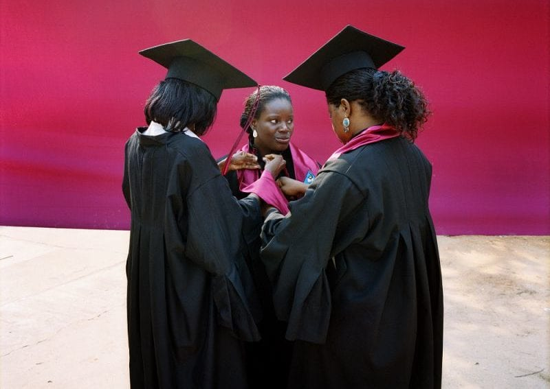 Three female students, wearing gowns and mortar boards