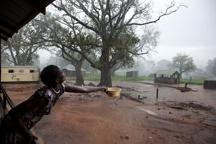woman standing on the verandah of a building holds out a bowl to collect rainwater